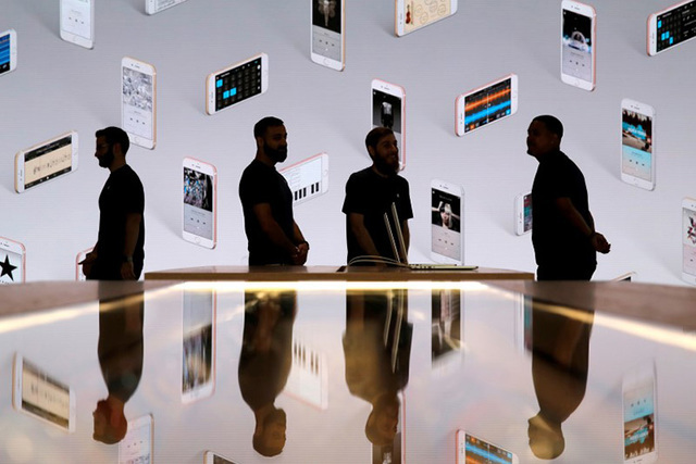 Store employees stand in front of a screen displaying iPhones during a preview event at the new Apple Store Williamsburg in Brooklyn, New York, U.S., July 28, 2016. Apple is expected to show off a ...