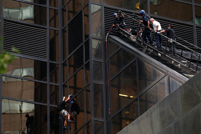 Officers from the New York Police Department watch as a man climbs using suction cups the outside of Trump Tower in New York, Thursday, Aug. 10, 2016. (Lucas Jackson/Reuters)