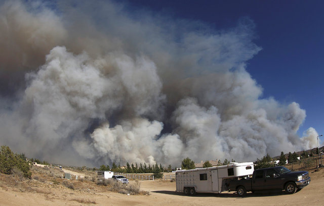 People evacuate their horses as smoke fills the skies in this photo taken with an extreme wide angle lens at the so-called Bluecut Fire in the San Bernardino National Forest in San Bernardino Coun ...