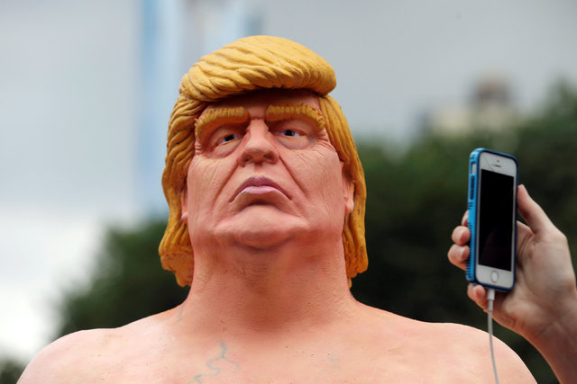 People photograph a naked statue of Donald Trump that was left in Union Square Park in New York City on August 18, 2016. (Brendan McDermid/Reuters)