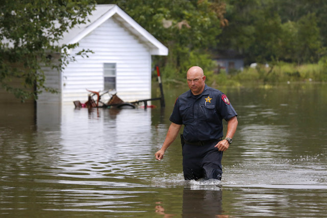 Sgt. Marc DeArmond of the Ascension Parish Sheriff's Office wades through flood waters after checking on a neighbor in Ascension Parish, Louisiana, Aug. 19, 2016. (Jonathan Bachman/Reuters)