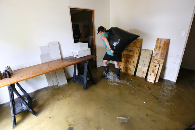 Brenda Covington carries a bag of clothing inside her friend, Wallace Floyd's flooded house in Ascension Parish, Louisiana, Aug. 19, 2016. (Jonathan Bachman/Reuters)