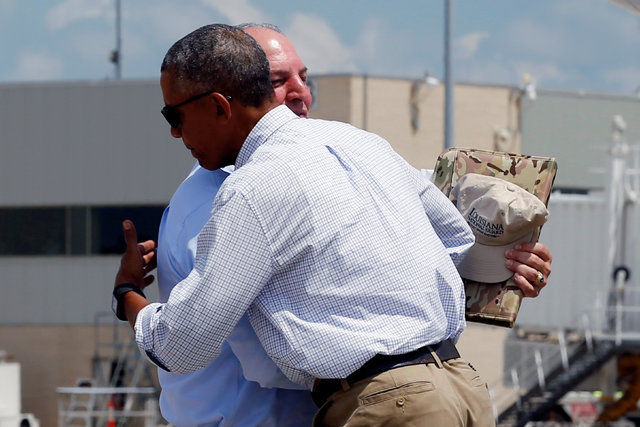President Barack Obama embraces Louisiana Gov. John Bel Edwards as he arrives aboard Air Force One at Baton Rouge Metropolitan Airport in Baton Rouge, Louisiana, Aug. 23, 2016. (Jonathan Ernst/Reu ...