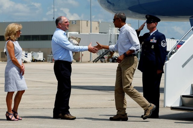 Louisiana Gov. John Bel Edwards, second left, and his wife, Donna, greet President Barack Obama as he arrives aboard Air Force One at Baton Rouge Metropolitan Airport in Baton Rouge, Louisiana, Au ...
