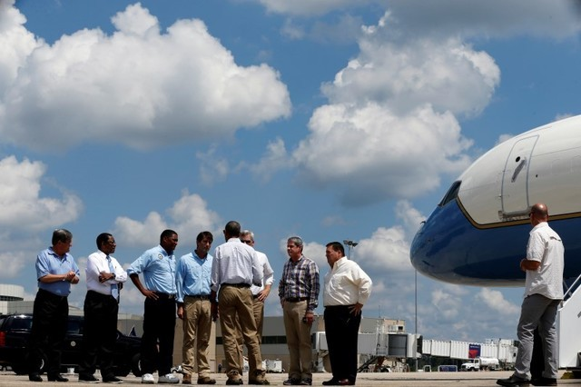 President Barack Obama (back to camera) speaks with local and state officials as he arrives aboard Air Force One at Baton Rouge Metropolitan Airport in Baton Rouge, Louisiana, Aug. 23, 2016. (Jona ...