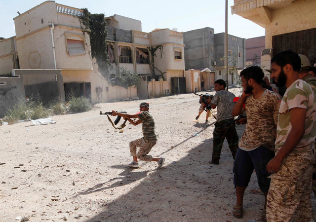 A member of Libyan forces allied with the UN-backed government fires a weapon toward Islamic State militants in neighborhood in central Sirte, Libya August 28, 2016. (Ismail Zitouny/Rueters)