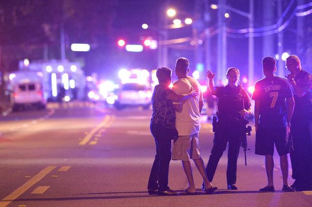 Orlando Police officers direct family members away from a fatal shooting at Pulse Orlando nightclub in Orlando, Fla., Sunday, June 12, 2016. (Phelan M. Ebenhack/AP)