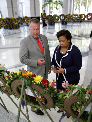 Orlando mayor Buddy Dyer, left, and Attorney General Loretta Lynch view a memorial at City Hall of 49 wreaths, one for each victim of the Pulse nightclub mass shooting, Tuesday, June 21, 2016, in  ...