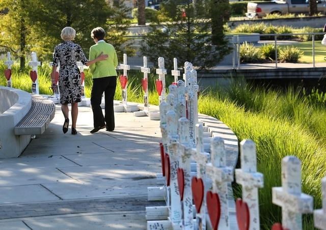 On the the one-month anniversary of the Pulse nightclub massacre in Orlando, Fla., Orlando city commissioner Patty Sheehan, right, and a friend take a last look at crosses honoring the 49 victims, ...