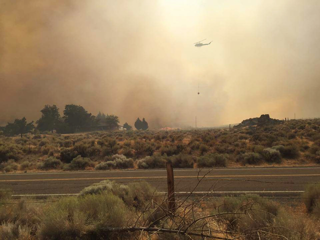 A helicopter flies over plumes of smoke from a wildfire in the community of Sutcliffe, about 35 miles north of Reno, Saturday, July 30, 2016. The wildfire was deterred Sunday from burning the trib ...