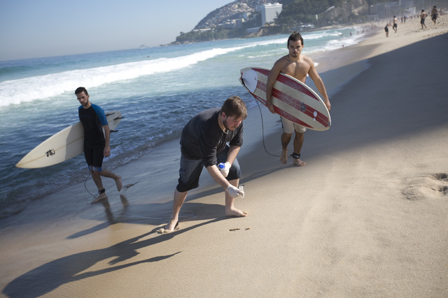In this July 11, 2016 photo, doctoral candidate Rodrigo Staggemeier collects samples of sand from Ipanema beach, for a study commissioned by The Associated Press, in Rio de Janeiro, Brazil. The 16 ...