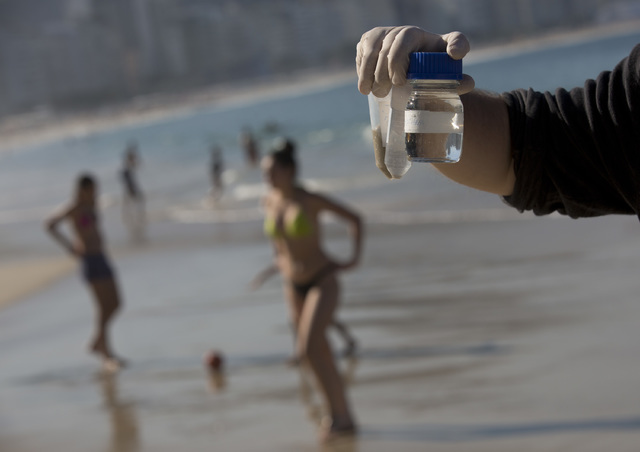 In this July 11, 2016 photo, doctoral candidate Rodrigo Staggemeier shows samples of water and sand from Copacabana Beach, collected for a study commissioned by The Associated Press, in Rio de Jan ...