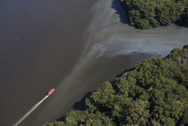 In this July 5, 2016 photo, an aerial view shows sewage moving into the canals that rim the Barra de Tijuca neighborhood near Olympic Park in Rio de Janeiro, Brazil. While local authorities includ ...