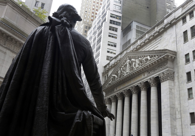 FILE - In this Oct. 2, 2014, file photo, the statue of George Washington on the steps of Federal Hall faces the facade of the New York Stock Exchange. U.S. stocks are little changed early Monday,  ...