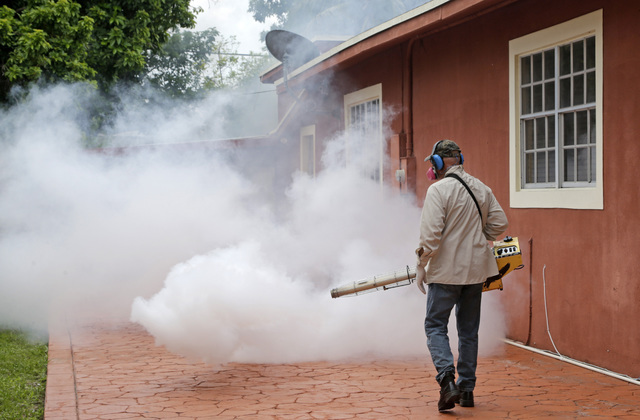 A Miami-Dade County mosquito control worker sprays around a home in the Wynwood area of Miami on Monday, Aug. 1, 2016. (Alan Diaz/AP)
