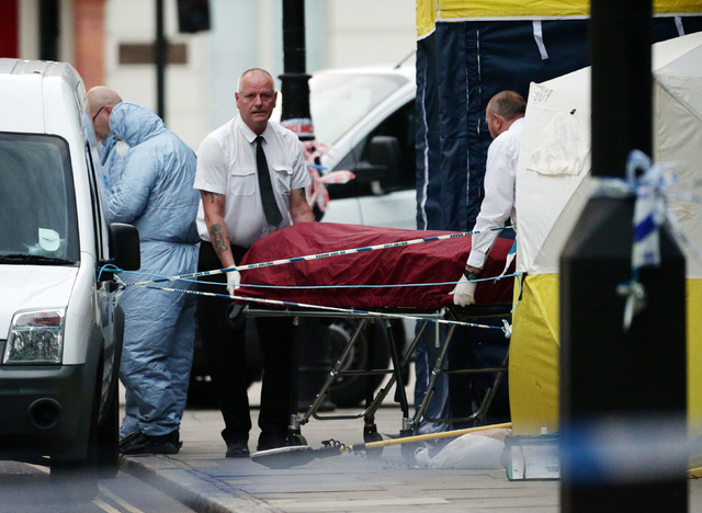 A body is removed from the scene in Russell Square in central London after a knife attack Thursday, Aug. 4, 2016. An American woman has died and others were injured in a knife attack. (Yui Mok/PA  ...
