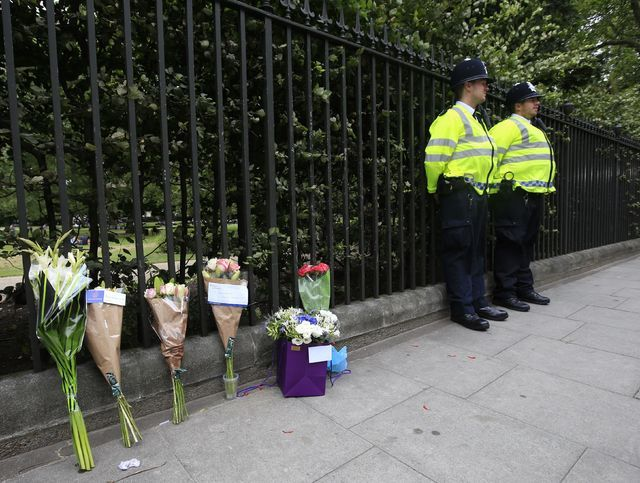 Floral tributes rest against railings Thursday Aug. 4, 2016, near the scene of a fatal stabbing on Wednesday night in Russell Square, London. London police say they have found no signs of radicali ...