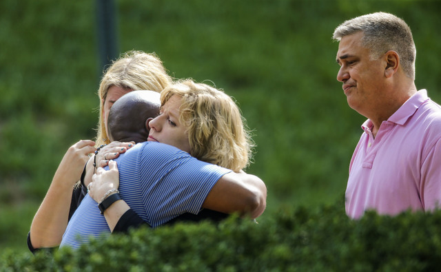 People hug near a crime scene, Tuesday, Aug. 2, 2016 in Roswell, Ga., where the bodies of Natalie Henderson and Carter Davis, both 17, were discovered by a delivery driver behind the Publix superm ...