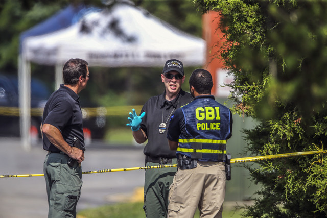 Police investigate a crime scene, Tuesday, Aug. 2, 2016, in Roswell, Ga., where the bodies of Natalie Henderson and Carter Davis, both 17, were discovered by a delivery driver behind the Publix su ...