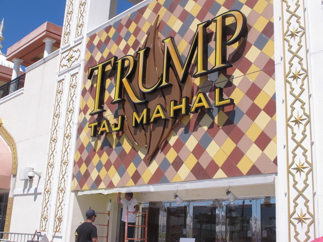 A worker carries out repairs to a facade of the Trump Taj Mahal casino in Atlantic City, N.J. on Thursday Aug. 4, 2016,a day after owner Carl Icahn announced he would close the casino after Labor  ...