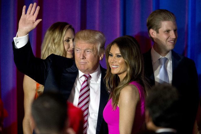 In this June 7, 2016 file photo, Republican presidential candidate Donald Trump waves at supporters as he leaves the stage with his wife Melania after a news conference at the Trump National Golf  ...
