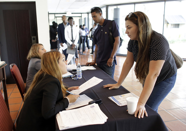 In this Tuesday, July 19, 2016, photo, Claudia Caballero, district manager for Aldi, left, talks with job applicant Raisa Rickie at a job fair in Miami Lakes, Fla. On Wednesday, Aug. 10, 2016, the ...