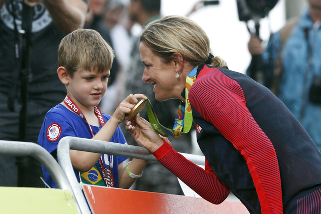 Cyclist Kristin Armstrong of the United States, right, shows her gold medal to his son Lucas William Savola after winning the women's individual time trial event at the 2016 Summer Olympics in Pon ...