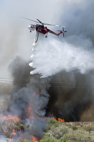 A helicopter makes a water drop on a wildfire as it burned near Cleghorn Road in the Cajon Pass in California, Tuesday, Aug. 16, 2016. (James Quigg/The Daily Press via AP)