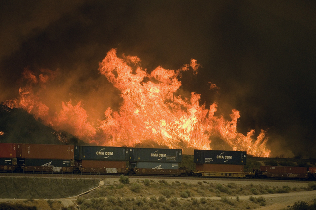 Flames erupt on a hillside alongside one of the main rail routes connecting Southern California with points north and east as a wildfire rages out of control in Cajon Pass north of Devore, Calif., ...