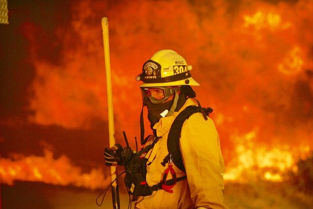 A firefighter prepares to battle a wildfire in the Cajon Pass in San Bernardino county, Calif., on Tuesday, Aug. 16, 2016. The wildfire that began as a small midmorning patch of flame next to Inte ...