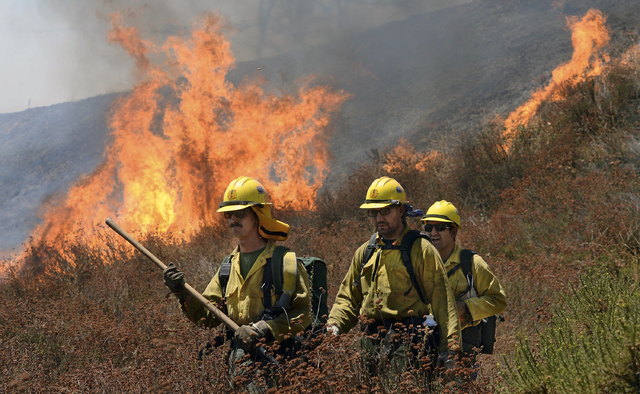 Firefighters battle the Blue Cut Fire along Swarthout Canyon Road in the Cajon Pass, north of San Bernardino, Calif., Tuesday, Aug. 16, 2016. (Will Lester/The Sun via AP)