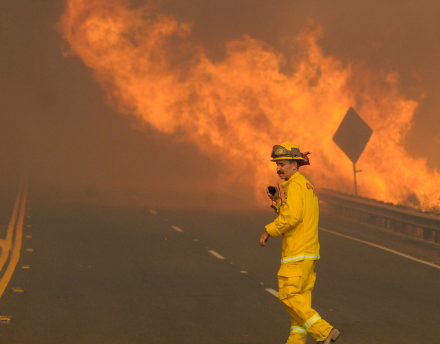 A CalFire firefighter begins clearing Highway 138 east of the Interstate 15 as a wildfire burns in California, Tuesday, Aug. 16, 2016. (James Quigg/The Daily Press via AP)