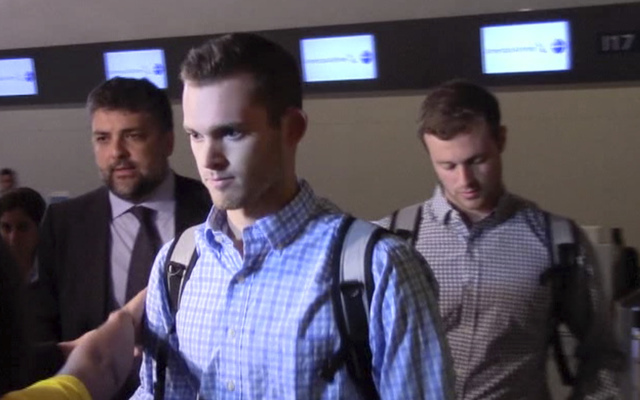In this image made from video, American Olympic swimmers Gunnar Bentz and Jack Conger walk in the departure area after checking into their flight at the airport in Rio de Janeiro, Brazil, Thursday ...