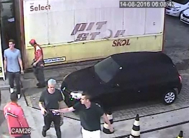 In this Sunday, Aug. 14, 2016 frame from surveillance video released by Brazil Police, swimmer Ryan Lochte, second from right, of the United States, and teammates, appear at a gas station duri ...