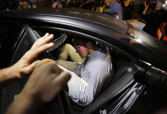 American Olympic swimmer Jack Conger gets into a car as he and fellow swimmer Gunnar Bentz leave a police station in the Leblon neighborhood of Rio de Janeiro, Thursday, Aug. 18, 2016. (Leo Correa/AP)
