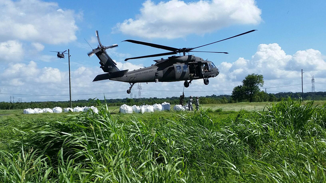 Soldiers with the 1023rd Engineer Company, 528th Engineer Battalion, attach supersac sandbags to a Louisiana National Guard UH-60 Blackhawk to be dropped at Alligator Bayou Control Structure by El ...