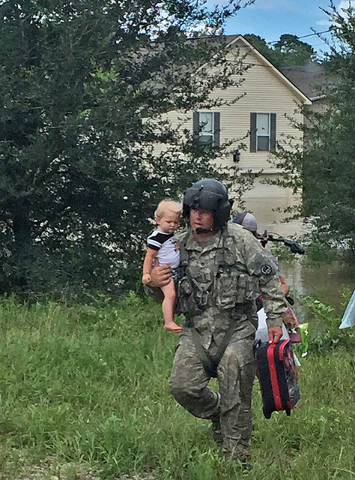 Sgt. Chad McCann of Deville, Louisiana, crew chief with F Company, 2-135th MEDEVAC, brings a young child to the waiting UH-60 Blackhawk to be taken to safety after flood waters threatened his home ...