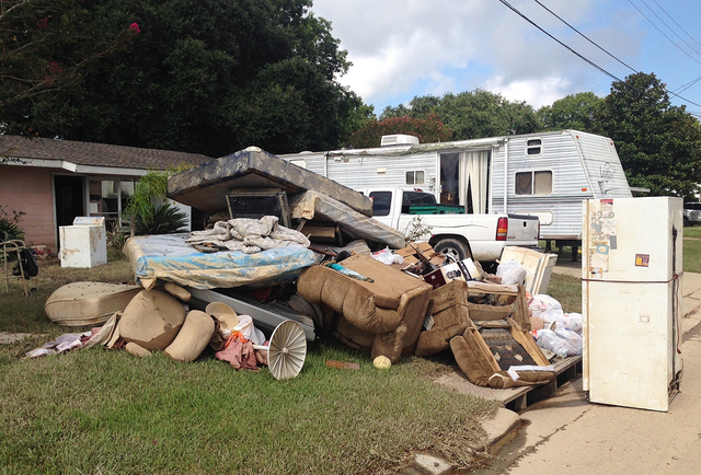 A growing pile of debris sits outside the flood-ravaged home of Carolyn and James Smith in Denham Springs, La. on Wednesday, Aug 17, 2016. Smith says she and four other adults will live for the ti ...