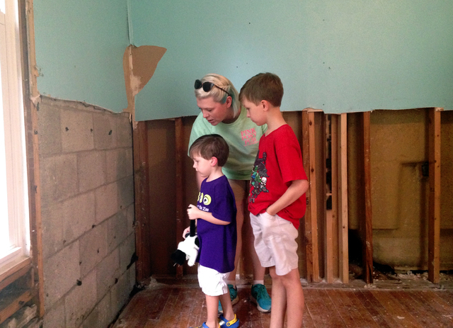 "Amanda Burge looks at flood damage with two of her three children Aiden, right, and Hudson, left, at her home in Denham Springs, La., Friday, Aug. 19, 2016. ""Everything is gone. School is ..."