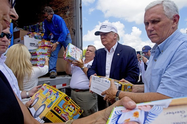 Republican presidential candidate Donald Trump and his running mate, Indiana Gov. Mike Pence, right, help to unload supplies for flood victims during a tour of the flood damaged area in Gonzales,  ...