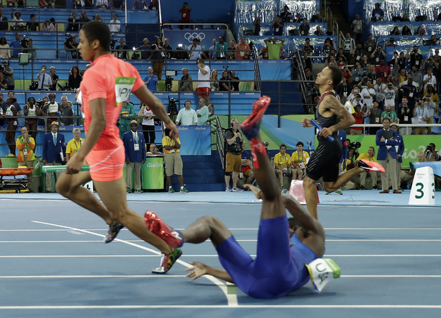 United States' Trayvon Bromell , falls over as Japan's Aska Cambridge passes him during the men's 4 x 100-meter relay final, during the athletics competitions of the 2016 Summer Olympics at the Ol ...