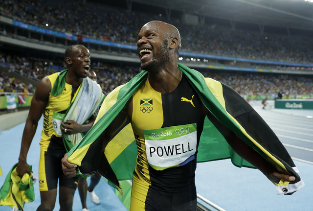 Jamaica's Asafa Powell, right, and Usain Bolt celebrate winning gold in the men's 4 x 100-meter relay final, during the athletics competitions of the 2016 Summer Olympics at the Olympic stadium in ...