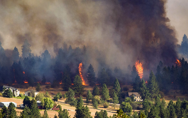 A fast-moving wildfire approaches homes on the north side of Beacon Hill in Spokane, Wash., Sunday, Aug. 21, 2016. (Colin Mulvany/The Spokesman-Review via AP)