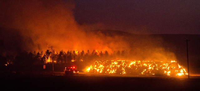 A fire truck moves along Highway 125 past a blazing stack of hay bales north of Walla Walla, Wash., during a large wildfire Sunday night, Aug. 21, 2016. (Greg Lehman/Walla Walla Union-Bulletin via AP)