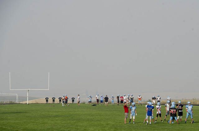 The Freeman High School football team practices amid a haze of smoke from the Yale Road fire on Monday, Aug 22, 2016, in Rockford, Wash. (Tyler Tjomsland/The Spokesman-Review via AP)