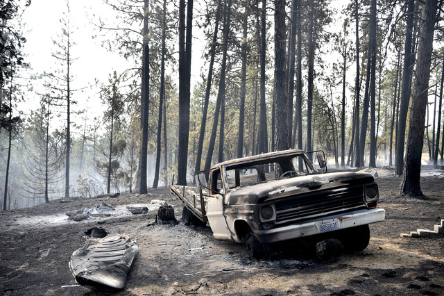 A charred truck is seen near the home of Julie Thayer and her husband, Art, on South Yale Road near Valleyford, Wash., on Monday, Aug 22, 2016. (Tyler Tjomsland/The Spokesman-Review via AP)