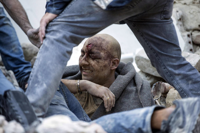 A man is pulled out of the rubble following an earthquake in Amatrice Italy, Wednesday, Aug. 24, 2016.  The magnitude 6 quake struck at 3:36 a.m. and was felt across a broad swath of central Italy ...