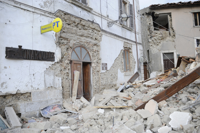 A post office is engulfed by rubbles in Arcuata del Tronto, central Italy, where a 6.1 earthquake struck just after 3:30 a.m., Wednesday, Aug. 24, 2016. The quake was felt across a broad section o ...