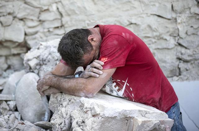 A man leans on rubble following an earthquake in Amatrice Italy, Wednesday, Aug. 24, 2016.  A strong earthquake in central Italy reduced three towns to rubble as people slept early Wednesday. (Mas ...