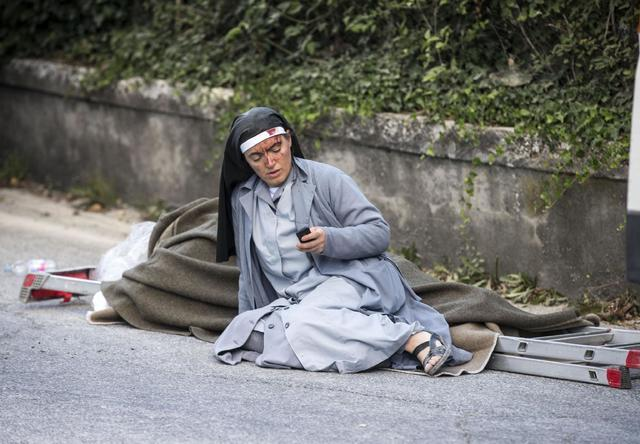 A nun checks her mobile phone as she lies near a victim laid on a ladder following an earthquake in Amatrice Italy, Wednesday, Aug. 24, 2016. (Massimo Percossi/ANSA via AP)